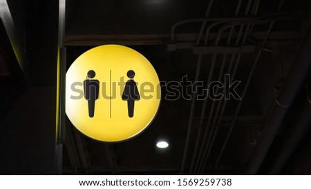 Circle lightbox restroom signage hang on wall
