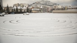 Circle Of Car's Footprint On White Snow In Parking Lot With Mountain In Background, Bozuyuk Town, Bilecik Province, Turkey.