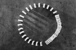 Circle of dominoes standing on gray background
