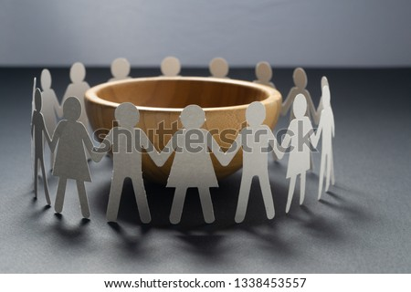 Circle of paper people holding hands in front of big empty bowl. Overpopulation, famine concept.