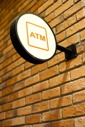 Circle shape ATM sign on brick wall