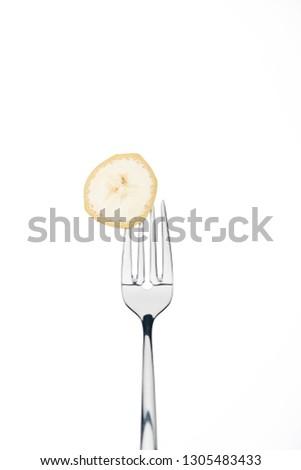 circle slice of fresh sweet banana on fork isolated on white isolated on white isolated on white #1305483433