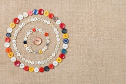 Circles of colorful sewing buttons on fabric texture background with copy space