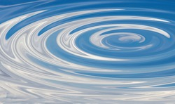 Circles on the water with a reflection of the blue sky with clouds.