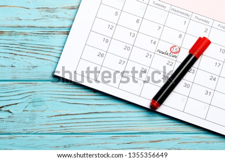 circling the date of the 15th day in the calendar. Concept of fertility chart, trying to have baby, Reminder Ovulation in graph, Planning of pregnancy. Red bow. On a blue wooden background.  Stock photo ©