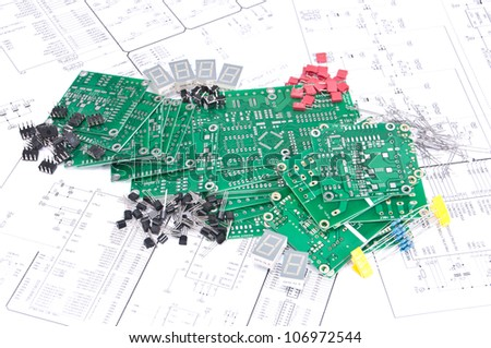Circuit boards and electronic components with schematics in background - stock photo
