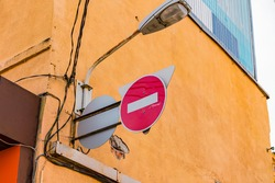 Circular do not enter prohibition traffic sign installed on the yellow facade of the building. Orange. Entrance. No entry. No-entry, Control. Restrictive road sign. Street lighting lamp