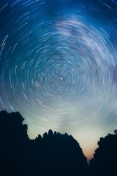 Circular motion of stars around the Polar Star in the blue sky. Earth's axis is revealed near the North Star, Polaris, in a 46 minute exposure.