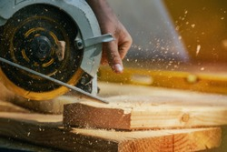 Circular Saw. Carpenter Using Circular Saw for wood beam