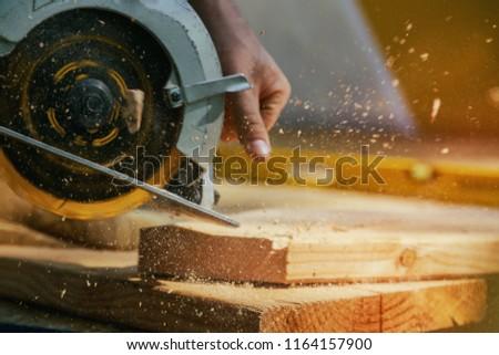 Circular Saw. Carpenter Using Circular Saw for wood beam