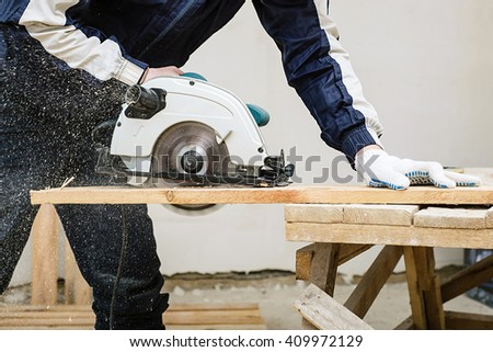 circular saw for cutting boards into the hands of the builder, the man sawed bars, construction and home renovation, repair and construction tool #409972129