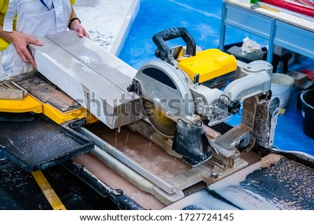 Circular saw in production. Sawing a concrete slab. Cut a stone plate with a circular saw. Stationary circular saw. Mason. Stone processing. Stone production. Build. Work on a construction site.