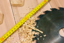 circular saw lying on the desktop, including sawdust and tape-measure