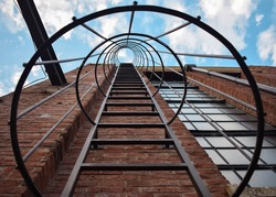 Circular staircase from below. Brown brick wall. Cloudy and blue sky
