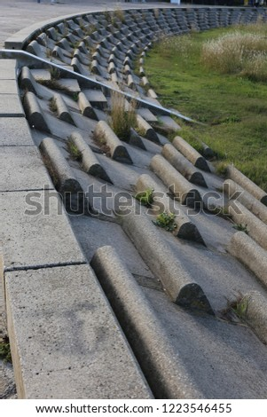 Circular terrace in circular concrete blocks with grass on the ground. Pattern of sits lighted by the sun. Abstract image of a frenc open air amphitheater with curving benches. #1223546455