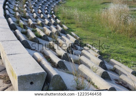 Circular terrace in circular concrete blocks with grass on the ground. Pattern of sits lighted by the sun. Abstract image of a frenc open air amphitheater with curving benches. #1223546458