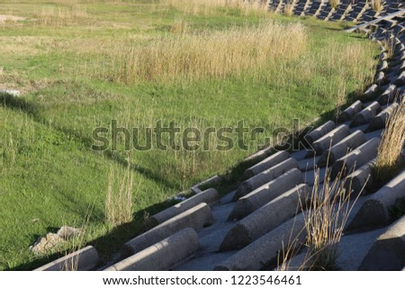 Circular terrace in circular concrete blocks with grass on the ground. Pattern of sits lighted by the sun. Abstract image of a frenc open air amphitheater with curving benches. #1223546461