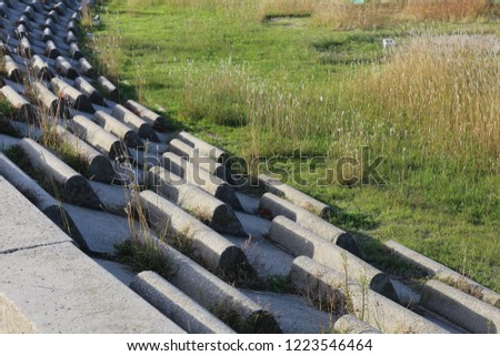 Circular terrace in circular concrete blocks with grass on the ground. Pattern of sits lighted by the sun. Abstract image of a frenc open air amphitheater with curving benches. #1223546464