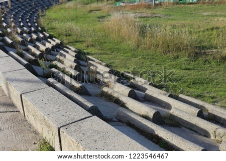 Circular terrace in circular concrete blocks with grass on the ground. Pattern of sits lighted by the sun. Abstract image of a frenc open air amphitheater with curving benches. #1223546467
