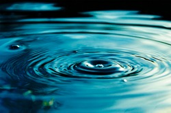 Circular waves and ripples in the water from a drop falling. Natural background blue water with circles and sky reflection.
