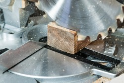 Circumcision of a square board with a circular saw, with slivers flying to the sides, close-up