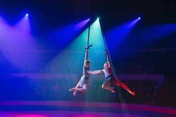 Circus actress acrobat performance. Two boys perform acrobatic elements in the air
