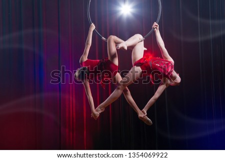 Circus actress acrobat performance. Two girls perform acrobatic elements in the air ring. #1354069922