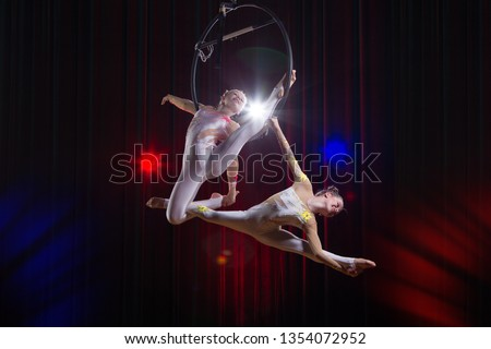 Circus actress acrobat performance. Two girls perform acrobatic elements in the air ring. #1354072952
