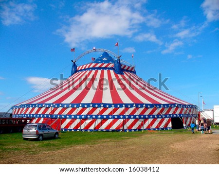Circus big top tent in field decorated with stars and stripes.