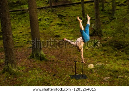 Circus performer balancing on one arm in a green forest #1285264015