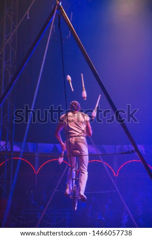 Circus performer juggling on slackwire #1466057738