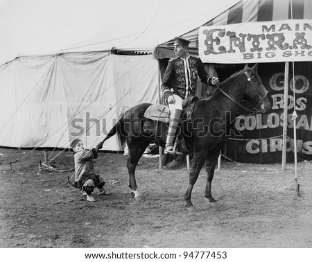 Circus performer pulling horses tail - stock photo