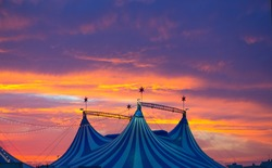 Circus tent in a dramatic sunset sky colorful orange blue with lights