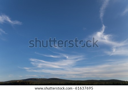 Cirrus clouds over forested hills.