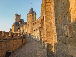 Cité de Carcassonne. Stony street of the famous, fortified, old city Carcassonne, Occitanie region, France. A beautiful medieval castle at sunset in the background of blue sky. High walls with towers.