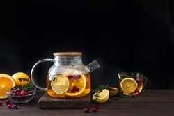 Citrus and berry tea with cranberries, lemon, oranges and thyme in a glass teapot on dark wooden table, copy space. Fruit tea. Seasonal winter autumn hot drink.