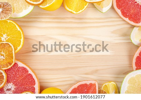 citrus frame template on wooden background. Fresh citrus fruits. Top view of sliced citrus fruits. Frame made of citrus fruits slices on wood planks. flatlay. copy space