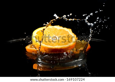 citrus fruit falling in water drops splashing everywhere. Concept of freshness and purity.