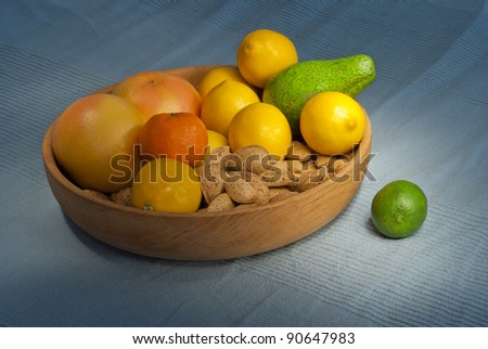 Citrus fruits, avocado and almonds in wooden bowl
