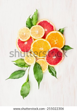 Citrus fruits composing with green leaves on white wooden background #255022306