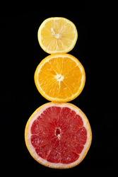 Citrus fruits, grapefruit, orange and lemon round fruits on a black background. Natural vitamins c. Exotic food.