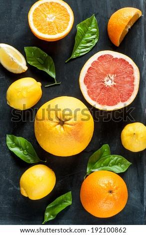Citrus fruits (lemon, grapefruit and orange) with fresh wet leaves on black chalkboard background - still life from above