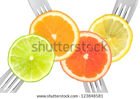 citrus fruits on forks isolated against white background