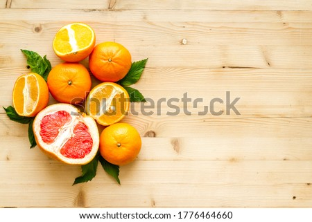 Citrus fruits on wood background top view