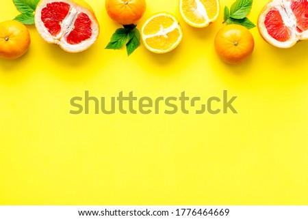 Citrus fruits on yellow background top view