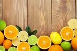 Citrus fruits. Oranges, limes and lemons. Over wood table background with copy space