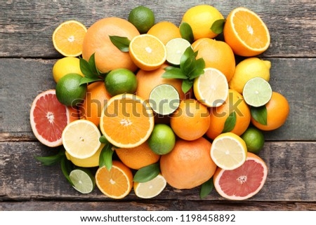 Citrus fruits with green leafs on grey wooden table #1198458892