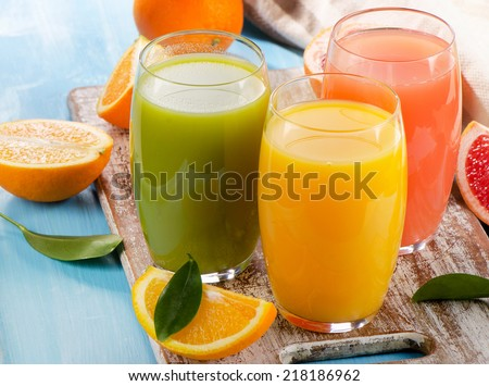 Citrus juice and fruits  on wooden background. Selective focus #218186962