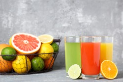 Citrus juice in glasses with fruits on grey wooden table