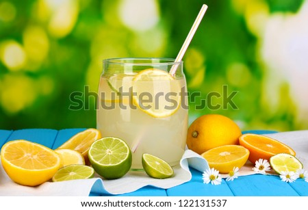 Citrus lemonade in glass bank of citrus around on blue wooden table on natural background